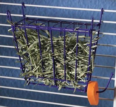 A hay rack hanging on a cage wall